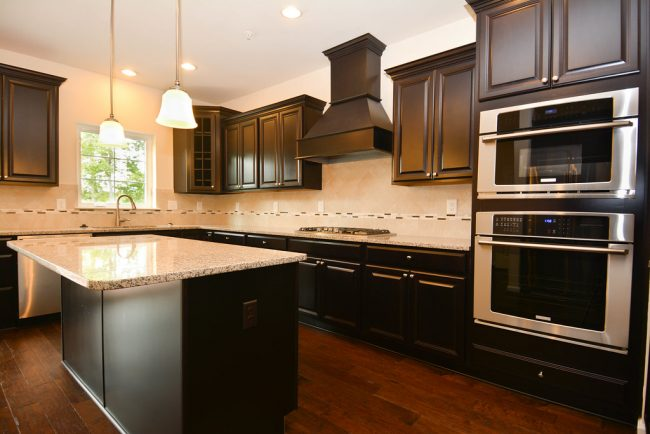 dark kitchen cabinets with double oven and gas stove