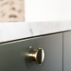 close up of silver knob on dark green drawer with white countertop