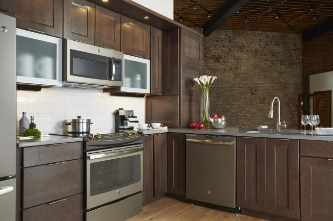 monochromatic kitchen cabinets and countertops in dark wood and dark brown/grey countertops