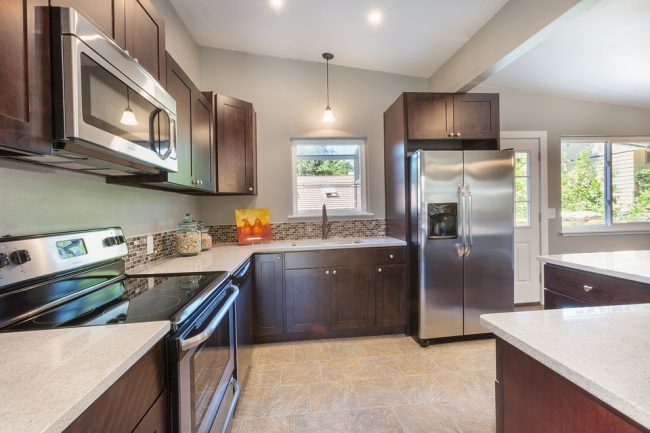 brown kitchen cabinets with beige countertops and stainless steal appliances facing a small window